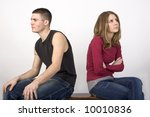 Couple sitting on a bench with their backs to each other. - stock photo