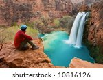 Woman sitting at the edge of a cliff watching Havasu Falls drop into it's turquoise pool. Havasu Canyon, Arizona. Havsupai Reservation. - stock photo