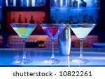 cocktail drinks and shaker on a bar, blurry bar background - stock photo