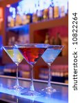 cocktail drinks on a bar, blurry background with bottles - stock photo