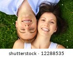 a happy and smiling couple is cuddle on a green meadow - stock photo