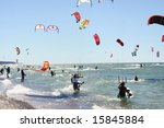 A lot of people kiteboarding in sunny day - stock photo