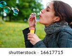 girl blow soap bubble against a background grass - stock photo