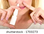 Woman spraying nasal spray in nostril and holding other nostril for effectiveness. - stock photo