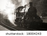 vintage unmarked steam train entering old fashioned station - stock photo