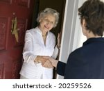 Smiling senior woman greeting visitor at the front door - stock photo