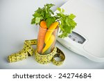 healthy vegetables in a glass surrounded by a measuring tape, bathroom scales in background - stock photo