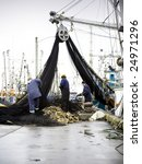 Fishermen at work, preparing fish nets - stock photo
