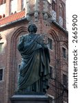 The statue of famous astronomer Nicholas Copernicus in Torun City (listed among the UNESCO World Heritage Sites). Historic Town Hall in background. - stock photo