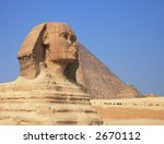 Ancient egyptian Sphinx of Giza with great pyramid of Cheops on the background - stock photo