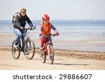 Mother and daughter riding on bicycles along beach - stock photo