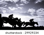 race horses jumping over a hurdle at speed photographed in silhouette with room for titles - stock photo