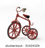 tiny red toy vintage metal tricycle on white background - stock photo