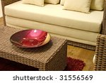 Close up of rattan table with red decoration dish. - stock photo