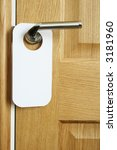 Blank do-not-disturb sign on a door handle. Vertical. - stock photo