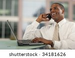 Smiling African American man talking on cell phone at desk with computer - stock photo
