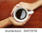 Coffee Cup betwen two hands in a yin and yang manner - stock photo