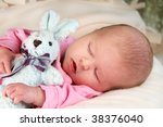 Baby girl sleeping with her arms around a bunny rabbit. - stock photo