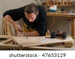 Young carpenter working with pneumatic chisel in his workshop - stock photo