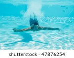 Man swimming with open eyes underwater in pool - stock photo