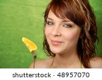 Beautiful young girl happily smiling and holding an orange on a fork, on a bright green background. - stock photo