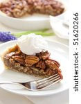 Pecan pie with generous dollop of whipped cream - stock photo