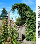 Unusual circular wooden garden gate with hollyhock flowers. - stock photo