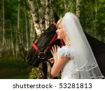 The bride in a wedding dress walks in wood with a horse - stock photo