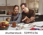 married couple arguing in kitchen with financial papers on counter - stock photo