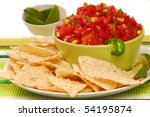 Freshly made tortilla chips with a corn and tomato salsa with limes - stock photo
