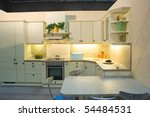 Modern kitchen in white with decoration, stools and table - stock photo