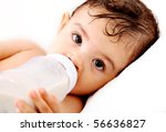 Baby drinking milk and looking at the camera. White Background - stock photo