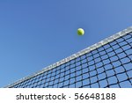 Yellow Tennis Ball Flying Over the Net Against a Clear Blue Sky - stock photo