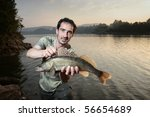 Happy fisherman presents zander, caught big fish - stock photo