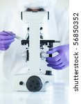 Forensic scientist examined evidence under microscope selective focus - stock photo