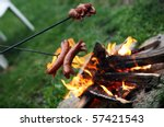 Roasting sausages on campfire in the garden - stock photo