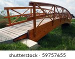 Wooden bridge over the small grassy ditch - stock photo