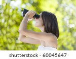Young woman using binoculars in summer forest - stock photo