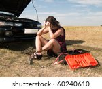 A beautiful young woman unsuccessfully trying to repair the car - stock photo