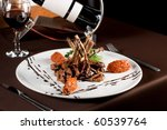 Roasted lamb chops with vegetables on decorated table - stock photo