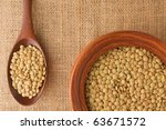 Green Lentil in a wooden bowl and on a spoon - stock photo