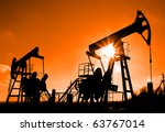 two working oil pumps silhouette against sun - stock photo
