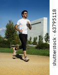 Man in sportswear running in a park - stock photo