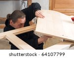 Young carpenter working in his workshop with hand tools - stock photo