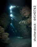 Rays of sunlight shining through inside an underwater cave. Jackfish alley, Ras Mohamed National Park, Red Sea, Egypt. - stock photo