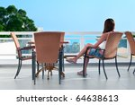 Young beautiful girl sitting on a chair on the balcony of the hotel and looks into the distance. One Caucasian woman is back side - stock photo