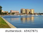 Condos and apartments on the shoreline of an inlet. Boats and yachts appear in the foreground amidst the serene reflections of the buildings this peaceful morning. - stock photo