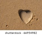 Heart shape of the sand near the sea - a symbol of love and Valentine's Day - a holiday on the southern beaches - stock photo