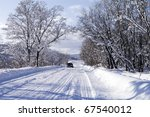 car goes on a winter country road - stock photo