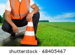 road worker closeup with orange posts at road - stock photo